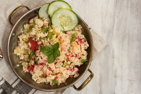 Tabbouleh Salad - Popular vegetarian Mediterranean dish made of fresh cucumber,tomatoes,parsley and coucous Banque d'images