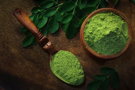 Overhead view of Moringa powder in an earthern pot on dark wooden background Фото со стока - 87726542