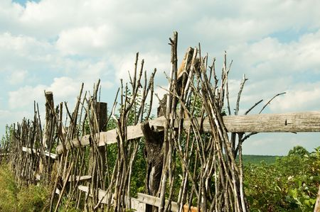 Old wooden fence in the village in summer photo