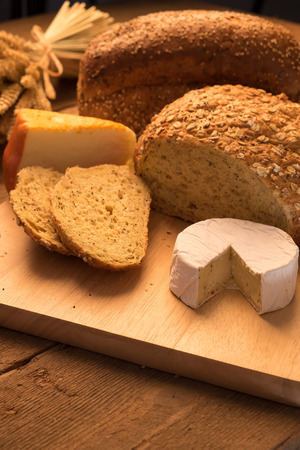 salut: Bread and cheese on chopping board and rustic background