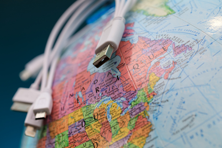 Globe and usb cables (toponymics are written in French). Focus on province of Ontario, Canada. Global communication. Conceptual interactions: Stock Photo
