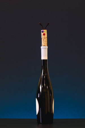 Funny cork on top of wine bottle. Picture of cork and wine bottle on fancy background. Aalcohol intoxication concept for banners and posters.