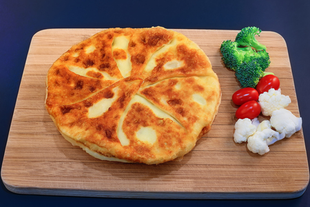 Appetizing round tart filled with feta cheese and served with vegetables on kitchen wooden table. Traditional tasty cheese pie, baked directly on the pan.
