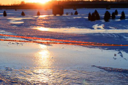 Warning sign of thin ice in the fishing village installed on the lake at risk of drowning. Warning or caution sign of drowning, frozen lake in the winter or at the beginning of the spring. Dangerous frozen lake. Stock Photo