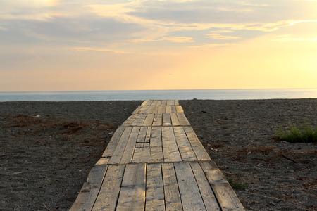 Footbridge on the Beach, Sand and Beautiful Sunset in the Sea Zdjęcie Seryjne