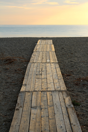 the silence of the world: Footbridge on the Beach, Sand and Beautiful Sunset in the Sea Stock Photo