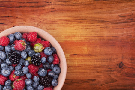retouched: Brown ceramic plate with berries on the left bottom corner of the wooden table with clipping path. Top view. Stock Photo