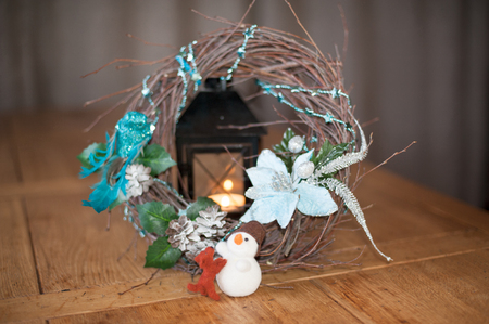 Festive decoration of the oak table Christmas wreath of willow branches on the fur skin in the company of a snowman and a dog with a candle in an old candlestick in the background. Imagens
