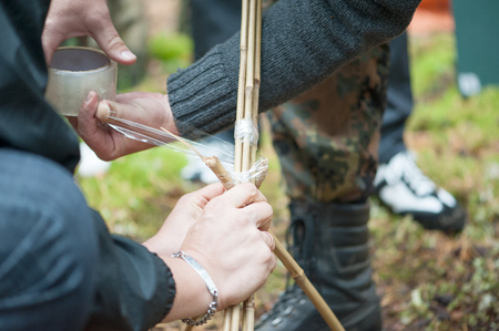 Close-up of hands of several people twirling bamboo sticks with transparent scotch