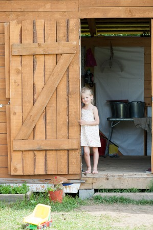 Barefoot blonde girl in summer sundress stands in the doorway of the shed against the background of household utensils Фото со стока