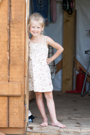 Barefoot blonde girl in summer sundress stands in the doorway of the shed against the background of household utensils Stockfoto