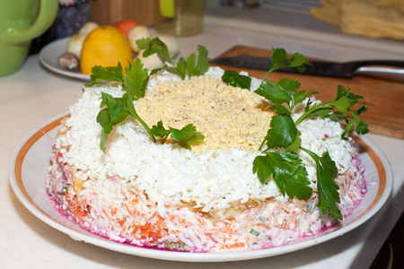 Traditional Russian salad herring under a fur coat on a large white dish decorated with greenery on the background of the kitchen table of the cutting board with a knife and kitchen utensils.