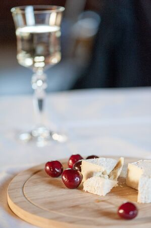Homemade camembert is beautifully cut on a wooden board and served with red cherry berries. With a glass of white wine in the background Stock Photo