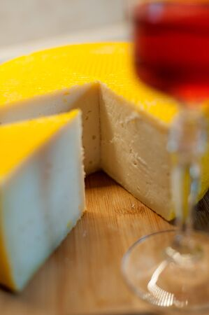 Home-made goat cheese and a glass of red wine on a wooden plank Stock Photo