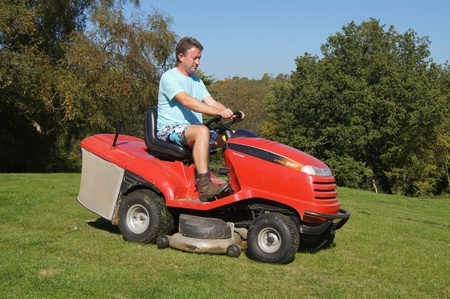 grass cutting: Man cutting the grass on a sit on lawn mower Stock Photo