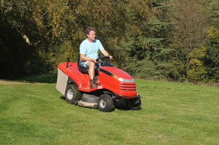 Man cutting the grass on a ride on lawn mower photo