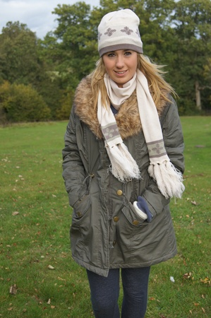 Pretty girl dressed in hat, scarf and gloves enjoying a chilly day out in the countryside photo