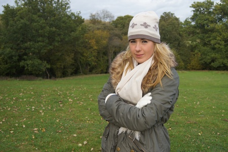 Pretty girl dressed in hat, scarf and gloves enjoying a chilly day out in the countryside Stock Photo - 10875192