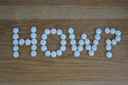 The word HOW? written using white glass pebbles on wooden background photo