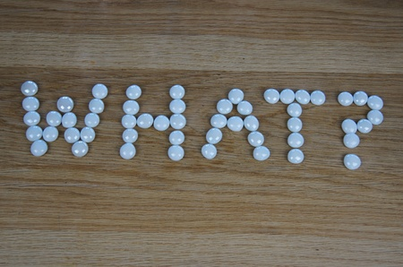 The word WHAT? written using white glass pebbles on wooden background photo