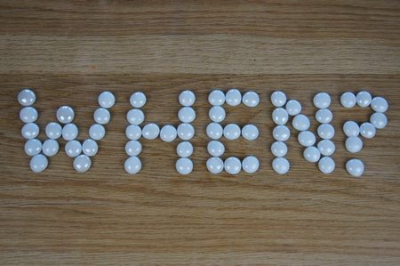 The word WHEN? written using white glass pebbles on wooden background photo