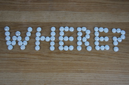 The word WHERE? written using white glass pebbles on wooden background photo