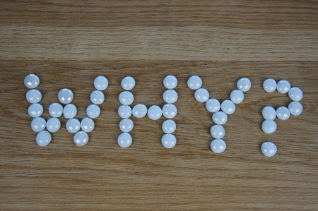 The word WHY? written using white glass pebbles on wooden background photo