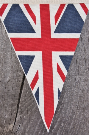 Triangular Union flag of UK on wooden background photo