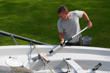 dingy: Middle aged man cleaning his dingy boat in his back yard after a days sailing Stock Photo