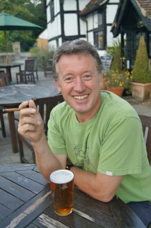 葉巻とイングリッシュパブ外ビールのパイントを楽しむ人 写真素材
