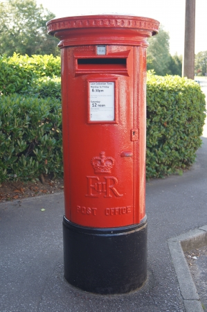 Traditional English red Royal Mail post box used for sending letters and parcels photo