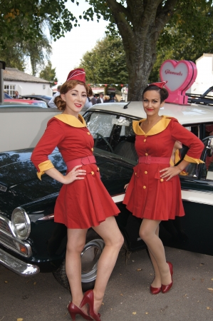 british girl: WEST SUSSEX, ENGLAND. SEPTEMBER 2012: Retro Glamcab girls posing by their taxi at the Goodwood Revival on 15th September 2012; Goodwood, West Sussex, England.