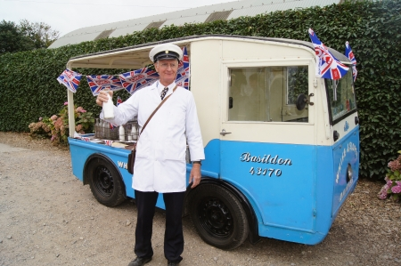 milkman: WEST SUSSEX, ENGLAND. SEPTEMBER 2012: Traditional 1950's milkman and milk-float at the Goodwood Revival festival on 15th September 2012; Goodwood , West Sussex, England. Editorial