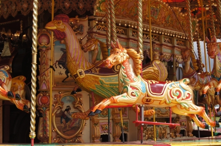 merry go round: WEST SUSSEX, ENGLAND. SEPTEMBER 2012: Vintage carousel with jumping horses at a traditional funfair at Goodwood Revival festival on 15th September 2012; Goodwood, West Sussex, England.