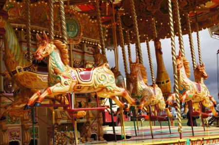 west sussex: WEST SUSSEX, ENGLAND. SEPTEMBER 2012: Vintage carousel with jumping horses at a traditional funfair at Goodwood Revival festival on 15th September 2012; Goodwood, West Sussex, England.