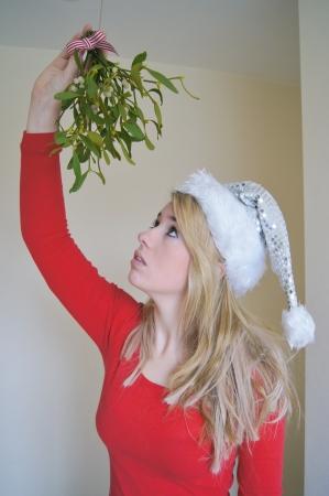 muerdago: Lonely girl llevaba sombrero de santa esperando un beso bajo el muérdago festivo