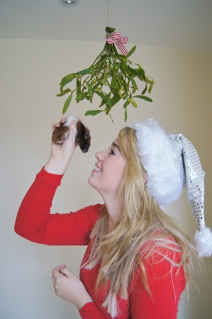 Girl wearing santa hat waiting for a festive kiss under the mistletoe with her pet hamster