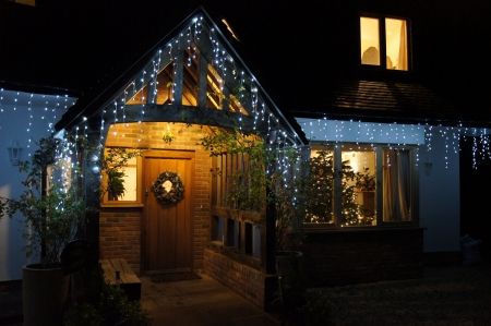 Festive home at night time with Christmas lights and tree through the window