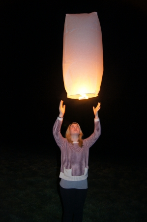 Girl releasing a Chinese lantern in remembrance or celebration photo