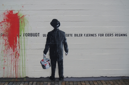 Banksy style graffiti of business man protesting against parking forbidden on public wall