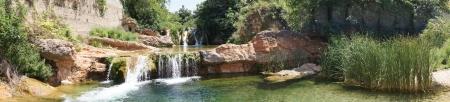 滝によって参加している岩のプールと川のパノラマの景色