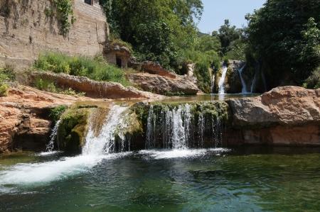 滝によって参加している岩のプールと川 写真素材
