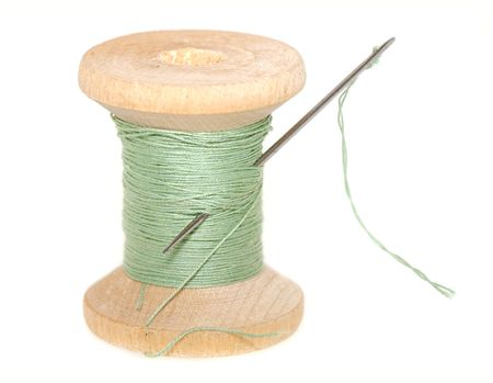 old items: old wooden spool of thread  with  needle isolated on white close-up Stock Photo