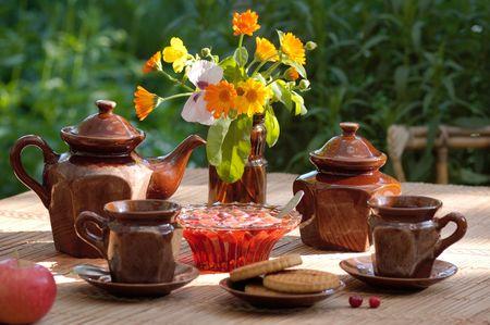 colores calidos: todav�a la vida en colores c�lidos de beber t� de la tarde con mermelada de fresa en el jard�n de verano