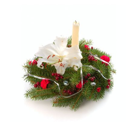Chrismas wreath with candle, red flowers, berries isolated on white