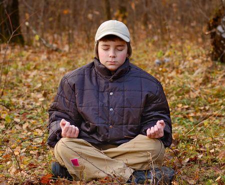 sitting boy meditate in autumn forest photo