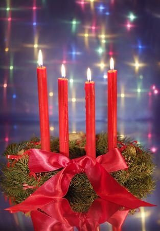Christmas wreath with red candles and pine cones against blue glowing backdrop photo