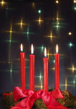 Christmas wreath with red candles against glow backdrop( focus on flame) photo