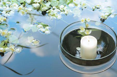 bianco candela in vetro galleggiante in acqua con Jasmin riflettendo cielo