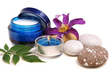 aging:  blue cosmetic cream,rebble, candle, flower on white